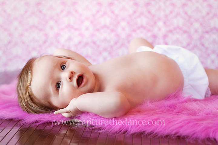 A 3 month old baby poses on a pink blanket.