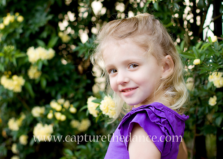Mikayla's stands for her children's portrait session amongst yellow flowers.