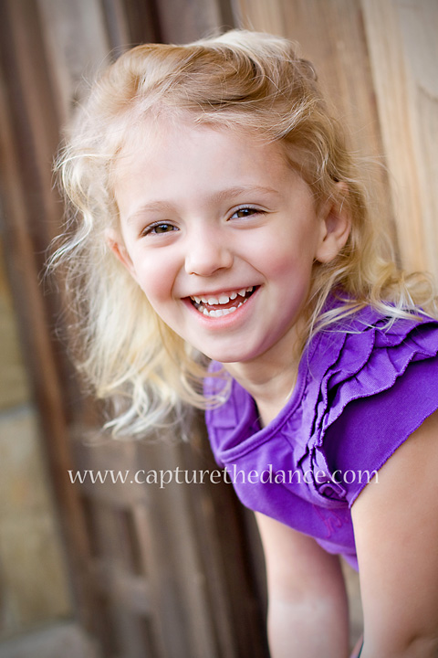 A child laughs during her outdoor portraits in The Woodlands.