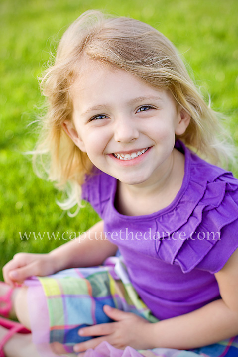 A young girl sits on the grass for her pictures on Lake Woodlands in Texas.