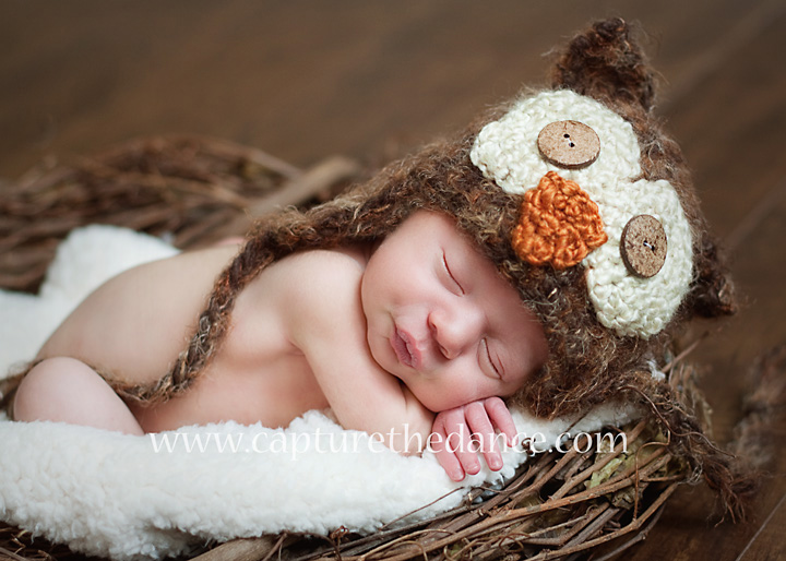 Newborn baby Jake sleeps in a nest with an owl hat.