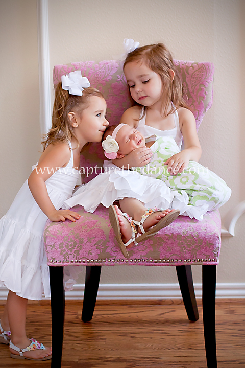 Two sisters lovingly adore their newborn baby sister as she smiles sweetly in her sleep.