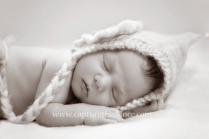 Black and white image of a sleeping newborn in a hat.