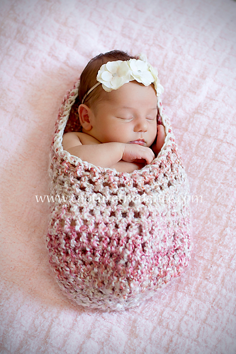 Newborn girl sleeping in a pink cocoon.