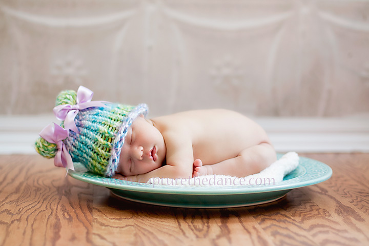 Baby girl laying on a blue platter in natural light.
