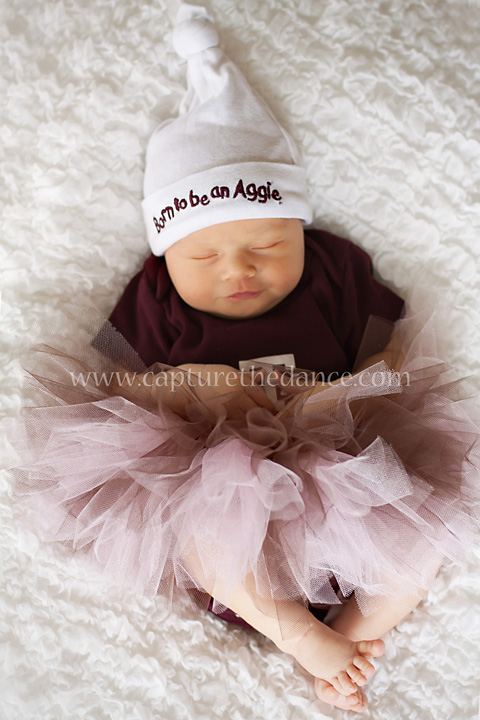 Baby in an Aggie outfit with a maroon tutu.