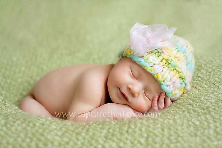 A picture of newborn baby Emma sleeping on a green blanket at my home studio in Spring TX.