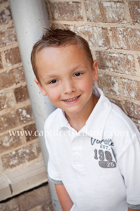 A Boy stands against a brick wall in The Woodlands.