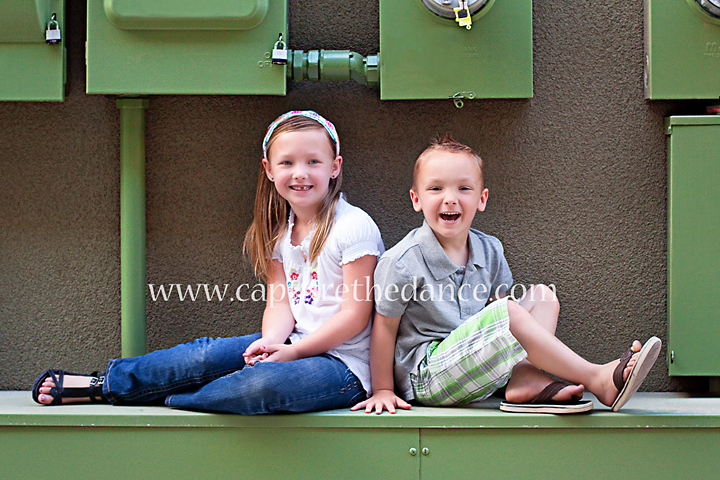 Two kids sit on colorful green meters on Market Street in The Woodlands.